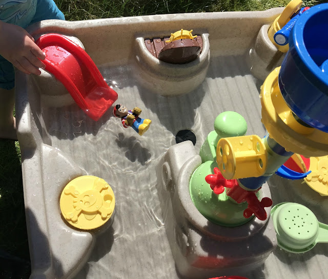 pirate toy going down toy water slide in a water table toy