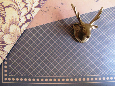 Selection of scrapbooking papers in black and gold, with a gold-painted stag head displayed on them.