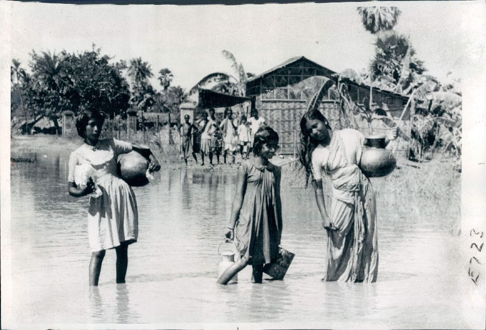Girls walk through flood waters on a road near Calcutta (Kolkata) as they carry drinking water in containers from distant places - 1959