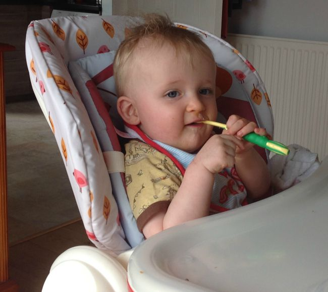 Baby in highchair with toothbrush