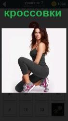 Девушка сидит на одном колене в спортивной форме и на ногах цветные кроссовки