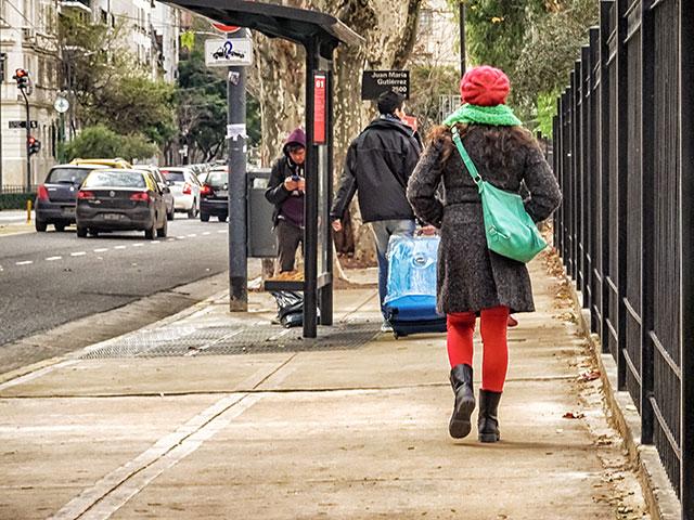 Joven de espaldas caminando con gorro rojo y tapado.