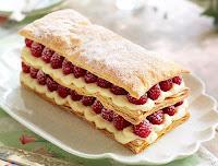 Bir tabakta arasında krema olan frambuazlı milföy tatlısı veya pastası