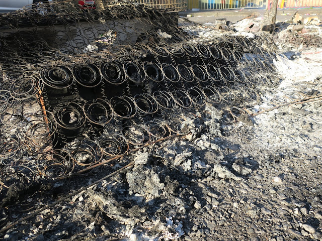 Mattress springs in sea of ash after bonfire the day before