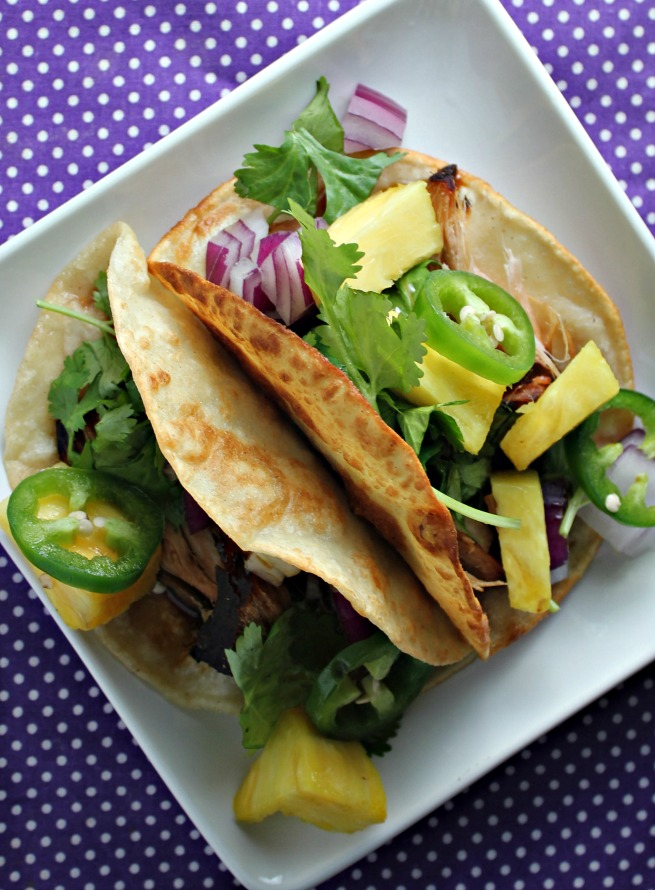 Slow cooker teriyaki pork tacos. Perfect for Taco Tuesday.  Easy and delicious.  Topped with Pineapple, cilantro, red onions and jalapenos and drizzled with teriyaki sauce.
