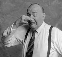 Black and white retro photo of a balding man with suspenders, holding his nose and making a disgusted face