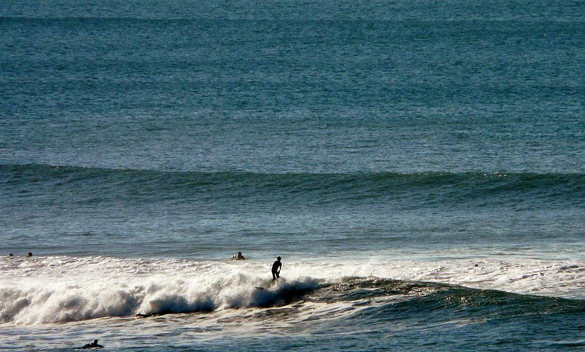 surfistas sobre una ola en sopelana