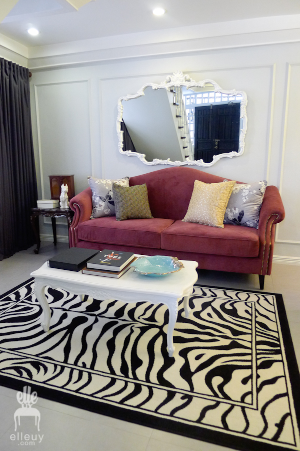 parisian chic living room with zebra rug and purple sofa