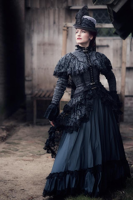 Woman wearing black lace gothic victorian dress. Bodice has layers of black lace that match the black lace and ostrich feather plume on her hat. women's gothic victorian clothing and fashion.