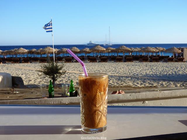 szklanka mrożonej kawy frappe na tle greckiego nieba i morza, grecka flaga w tle, parasole na greckiej plaży Mykonos