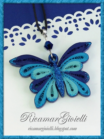 Ciondolo a farfalla realizzato in carta con la tecnica del quilling