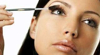 Mujer maquillando sus pestañas