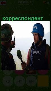 корреспондент в синей каске берет интервью с микрофоном