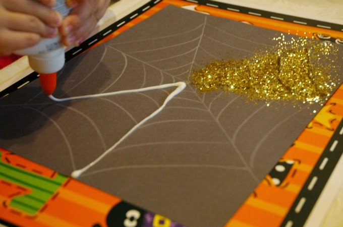 squeezing glue onto sparkly spiderweb glitter halloween craft