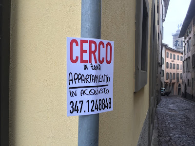 A sign on via Pelabrocco announcing someone looking to buy an apartment in the area.