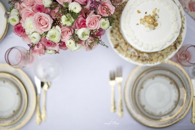 Table with gold dishes, cake and pink flowers