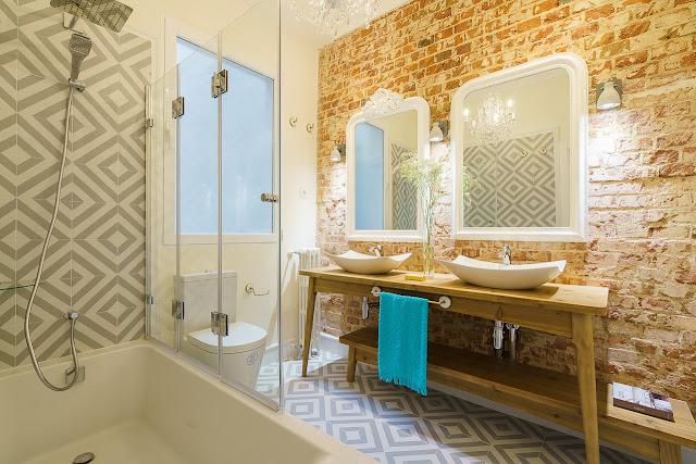 baie cu perete de caramida expusa si doua lavoare