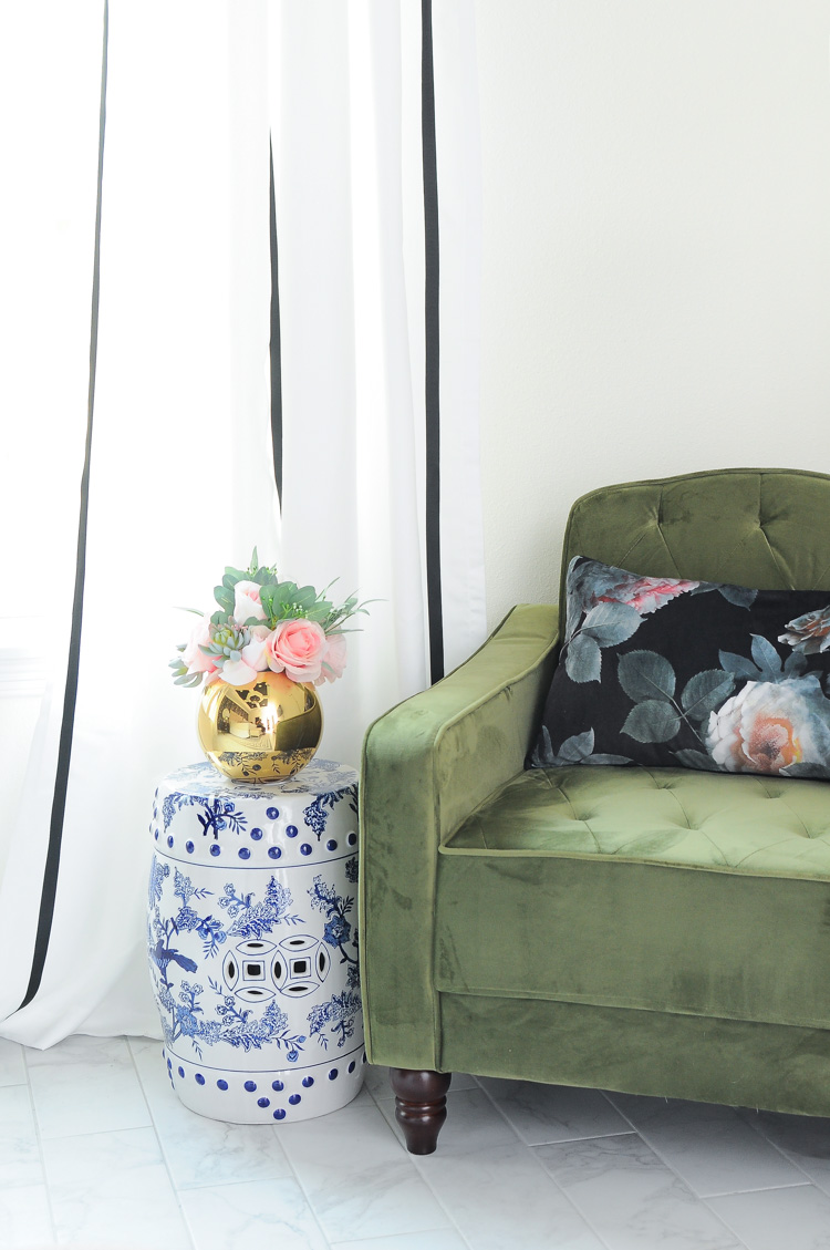 Love the mix of black and white and blue and white next to this gorgeous green tufted armchair in a master bedroom. Eclectic and chic!
