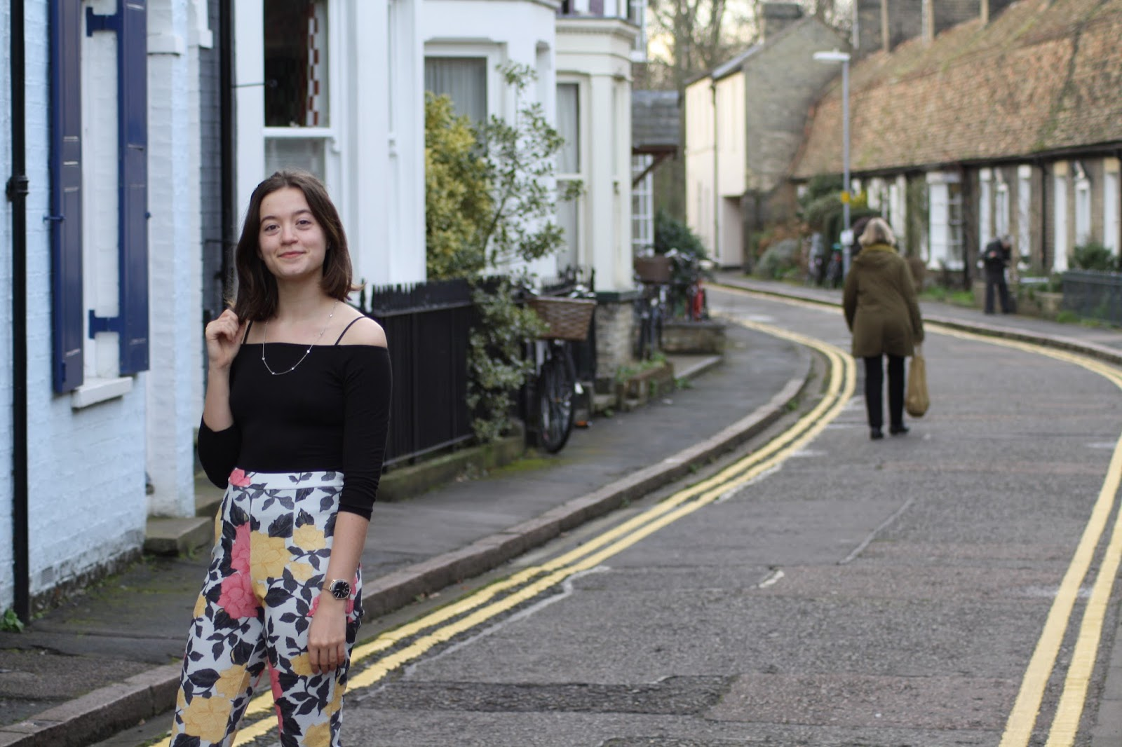 Abbey, a blogger, stands on a cute Cambridge street, playing with her hair with one hand
