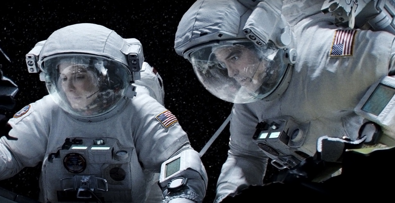 Astronauts in helmeted spacesuits looking at something off-screen