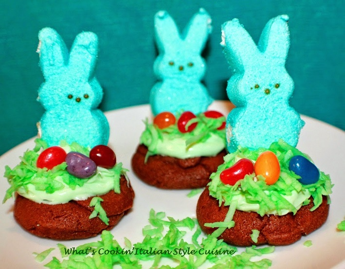 These are peeps on top of chocolate cookies that are frosted green with coconut and jelly beanst