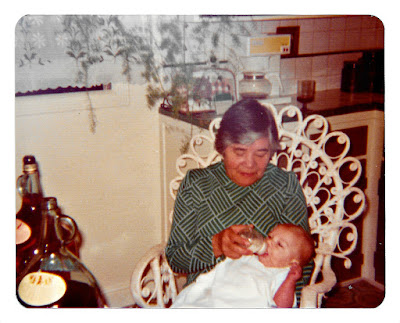 "Clara Aceituno—aka ""Mama Clara""—in 1976 at 1776 Sweetwood Drive in Broadmoor, California, nursing some random white baby with Almaden wine."