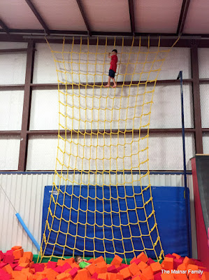 Jackson at the top of a giant floor to ceiling climbing net, nearly touching the ceiling.