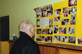 Weihbischof betrachtet Fotos der Kinder