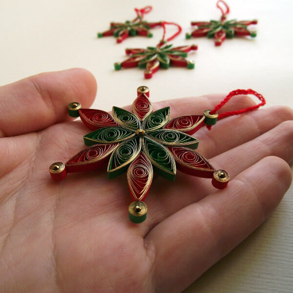 red and green quilled snowflake tree ornament with metallic gold edging