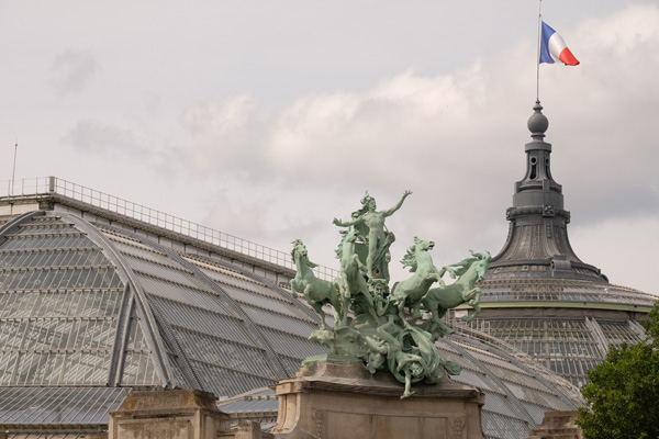 Sculpture with four horses and the glass and iron roof of the Grand Palais with the French flag waving in the breeze. Paris photos by Kent Johnson for Street Fashion Sydney.