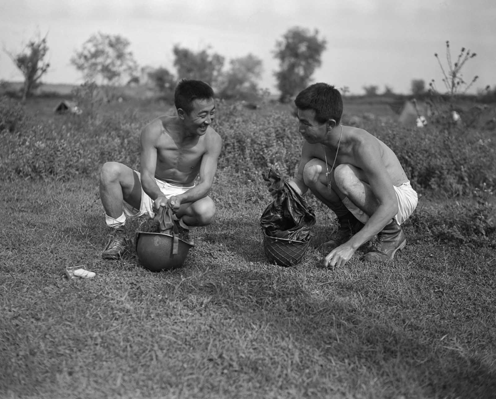 Shiro Yamato and Ginchi Masumotoya wash their uniforms in their helmets behind the lines during the invasion of Italy. October, 1943.