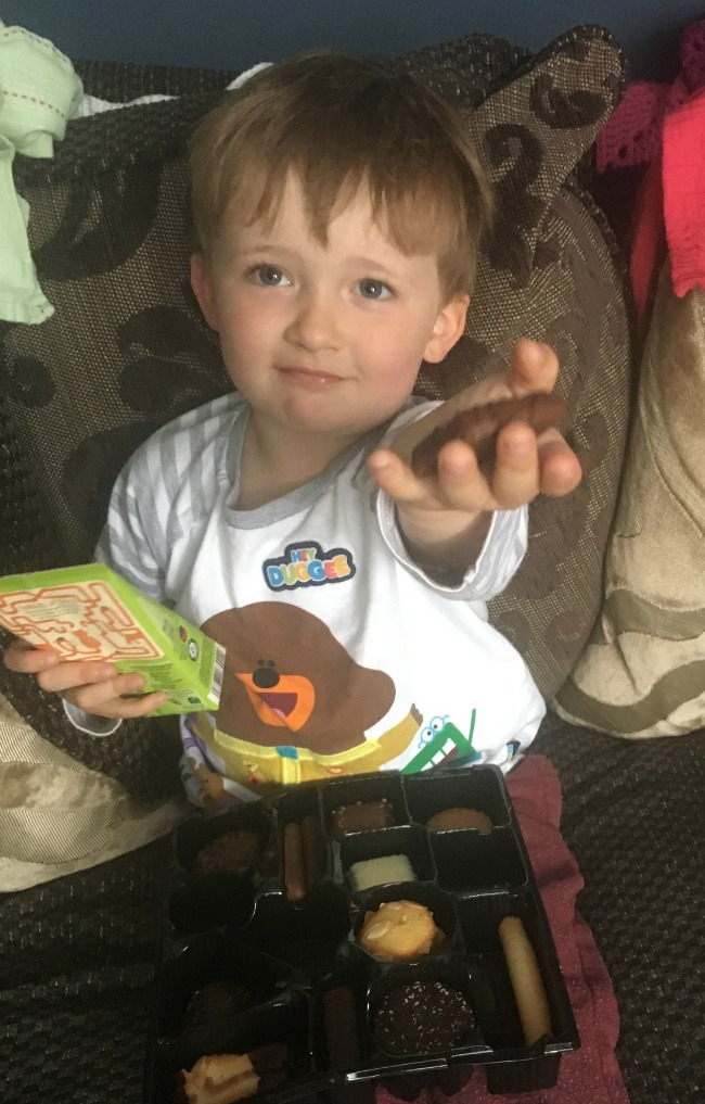 boy-holding-out-hand-offering-chocolate-biscuit