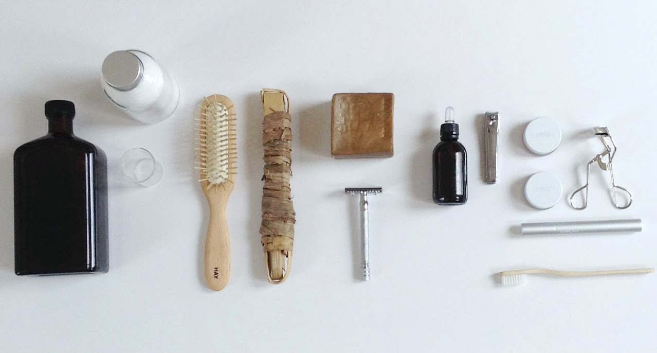 Zero Waste, Plastic Free Beauty and Grooming in Paris. For sustainable, green, plastic-free living. Homemade mouthwash, DIY tooth powder, glass cup for rinsing, sustainably harvested wooden toothbrush, siwak (miswak) sticks to replace floss, unpackaged Alep soap for cleaning and shaving, Merkur 25c safety razor, Buly 1803 grapeseed oil, RMS beauty cosmetics, bamboo toothbrush
