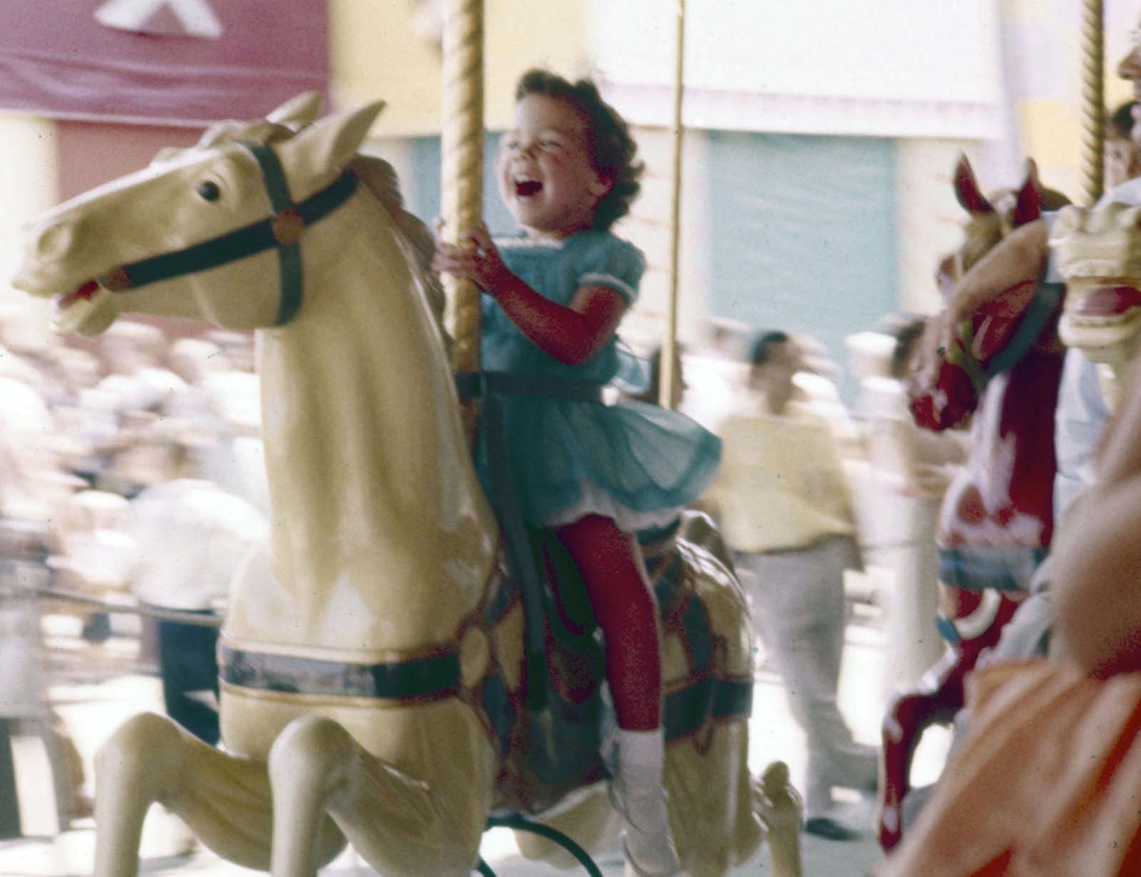 A little girl laughs with excitement while riding a carousel at Disneyland in July 1955.
