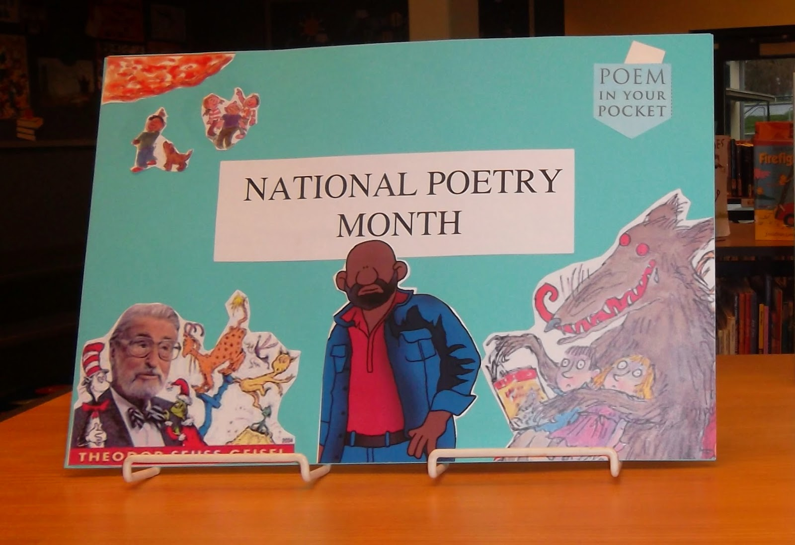 "Blue posterboard that reads ""National Poetry Month,"" decorated with images from the cover of a book by Jack Prelutsky, the ""Poem in Your Pocket"" pocket-shaped logo, an image from the cover of a book by Roald Dahl and Dr. Seuss surrounded by several of his characters"