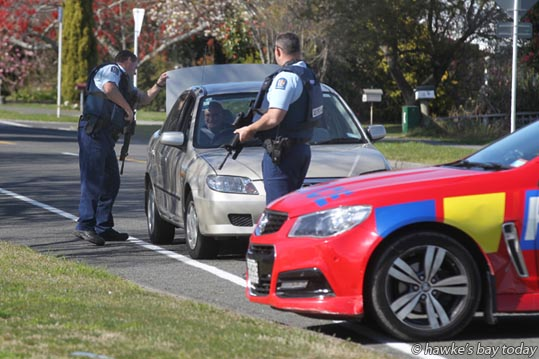 Armed police check out a car coming out of a cordon on Riverbend Rd, on the Maraenui side of Arnold St, Napier. photograph