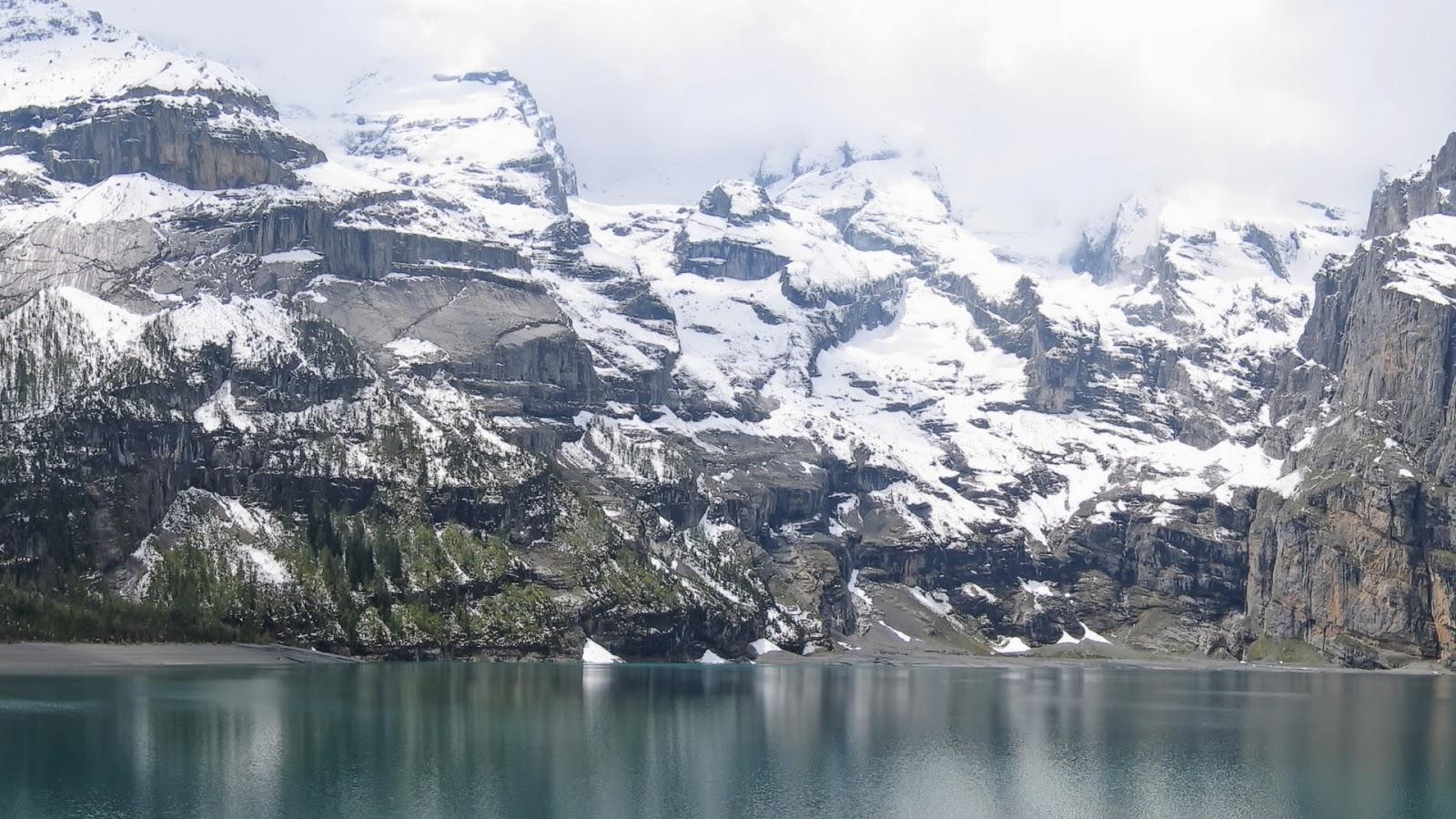 Een blauw meer hoog in de bergen met sneeuw