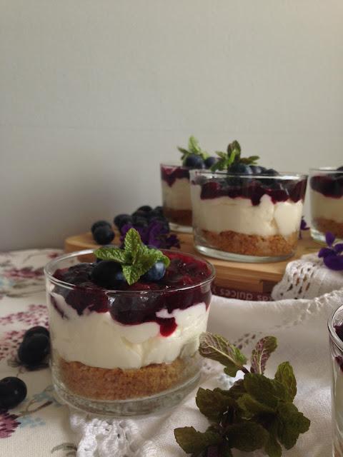 tarta de queso con mermelada de arandanos en vaso