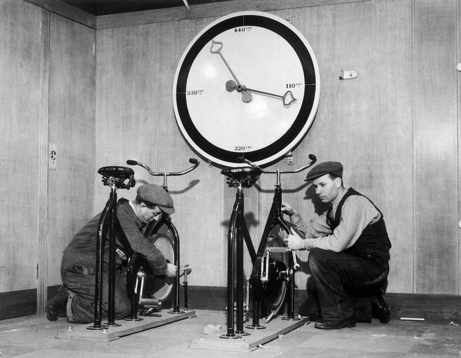 At the time of the installation of the English liner Queen Mary, workmen in the gymnasium of the ship are setting up exercise bikes, with an enormous meter indicating the distance covered. 1932.