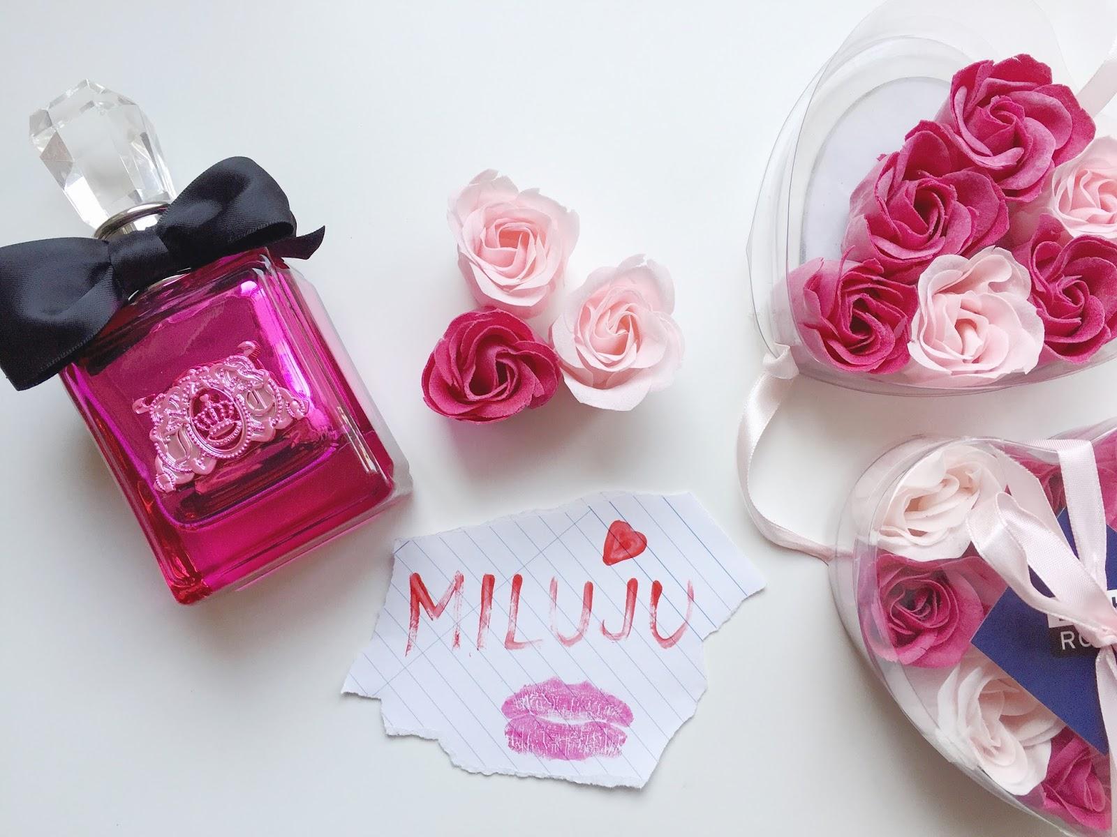 Parfém Viva La Juici Noir, růžové růže a rtěnkou napsaný nápis miluju na papírku, vše na bílém podkladu