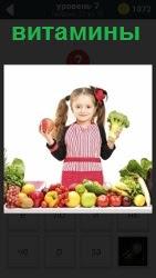 Маленькая девочка в руках держит яблоко и грушу в качестве витаминов. на столе лежат остальные фрукты