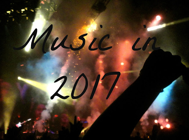 """Music in 2017"" text on background of lights and crowd at rock concert"