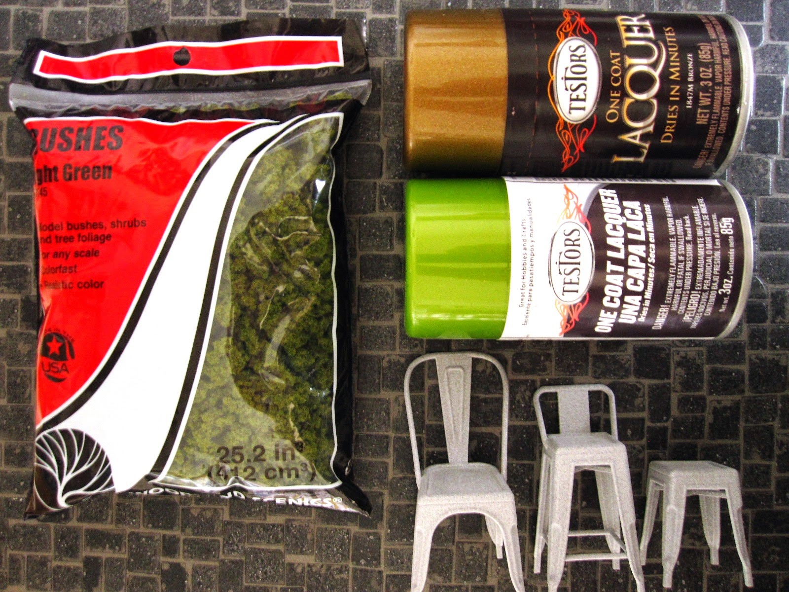 A bag of model railway bushes beside cans of copper and green metallic spray paint and three modern dolls' house miniature 3D printed cafe chairs.