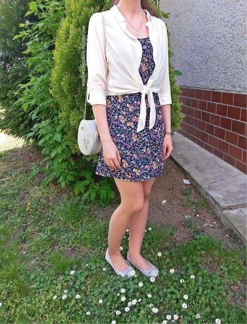 Biała wiązana koszula, granatowa sukienka w kwiaty, szara torebka i baleriny