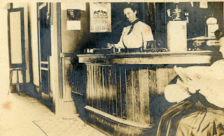 Mrs. Mattie Morris at the front desk of the St. Charles Hotel, Kerrville, 1909