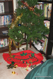 the tree with many of its decorations on the floor