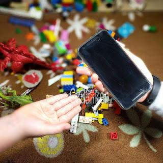 1 leere Kinderhand, 1 Kinderhand mit Smartphone; Spielzeug im Hintergrund;