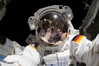 Alexander Gerst, astronauta da Nasa tira selfie no espaço.  Descrição: Foto com fundo escuro, Gerst de frente, na parte externa da estação espacial. Refletido no visor espelhado do capacete as mãos do próprio no instante da foto.