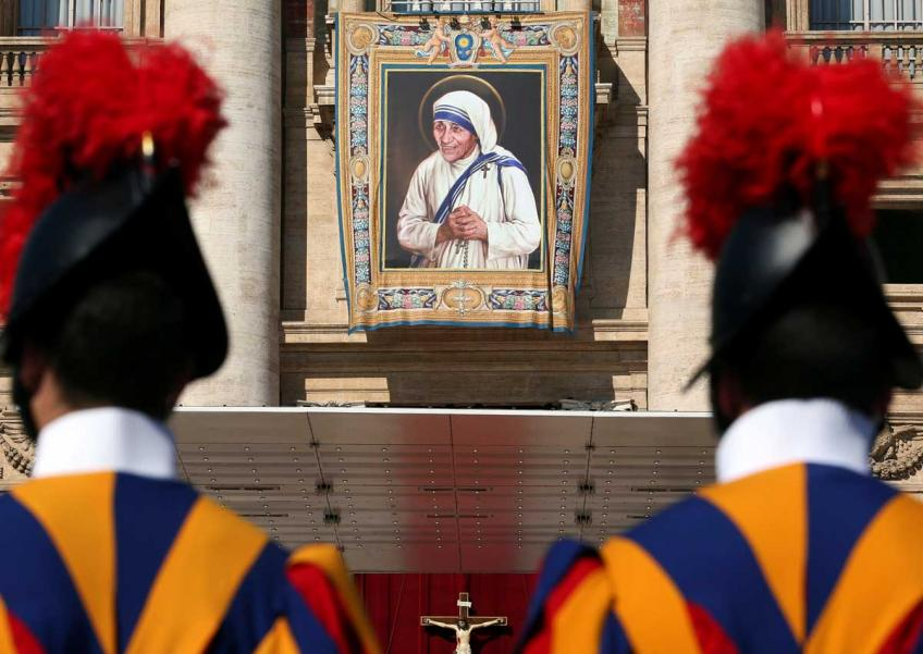 Swiss Guards stand in front of a tapestry depicting Mother Teresa of Calcutta before a mass, celebrated by Pope Francis, for her canonisation in Saint Peter's Square at the Vatican.