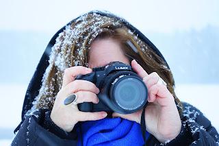 Mulher com capus, tirando foto na neve. Os cabelos cheios de neve como caspa.